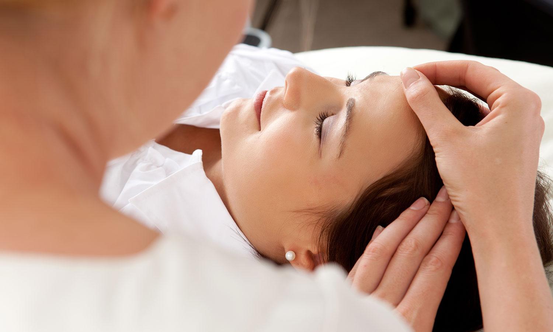 Naheaufnahme einer liegenden Frau mit geschlossenen Augen, die von der Therapeutin eine Stirnmassage erhält. -yler Olson/Shutterstock.com