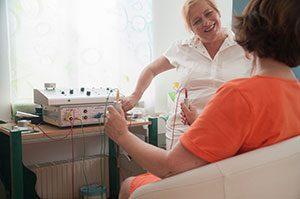 Patientin, mit Rücken zum Betrachter und speziellen Bioresonanz-Metallstiften in den Händen im Gespräch mit der behandelnden Ganzheitsmedizinerin. - Jamina Paukner/Pumperlgsund