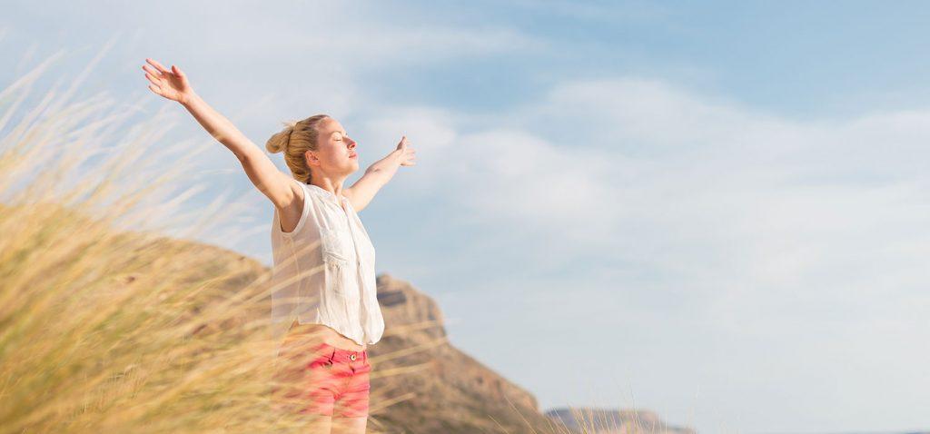 Frau, die mit ausgebreiteten Armen, geschlossenen Augen und sichtlichem Wohlbefinden vor blauem Himmel in einer Dünenlandschaft steht. - Matej Kastelic/Shutterstock.com