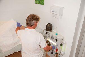 Der Therapeut steht neben dem auf einem Behandlungsbett liegenden Patienten und überwacht die Colon Hydro Darmspülung mittels dem entsprechendem Spezial-Gerät. - Jamina Paukner/Pumperlgsund