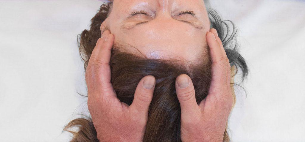 Kopf einer liegenden Frau mit geschlossenen Augen von oben zu sehen, die Hände des Craniosacral-Spezialisten sind an ihren Schläfen.