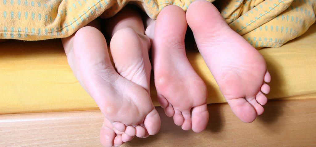 Nackte Fußsohlen von zwei unter einer gelb-gemusterten Decke liegenden Personen.