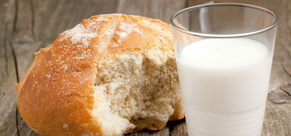 Ein Glas Milch mit einem angebrochenen Brötchen in Nahaufnahme. - Natasha Breen/Shutterstock.com