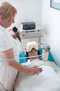 Patient am Rücken liegend mit Entspannungs- und Trance-Zustand fördernder Speziall-Brille und lärmdämmenden Kopfhörern. Die Hypnose-Ärztin steht neben ihm mit Mikro, sodass er nur ihre Stimme hören kann. - Jamina Paukner/Pumperlgsund