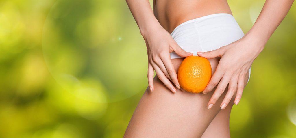 Nahaufnahme eines weiblichen Beins, Po im Anschnitt sichtbar. Sie hält mit beiden Händen eine Orange vor diese Stellen. - Billion Photos/Shutterstock.com