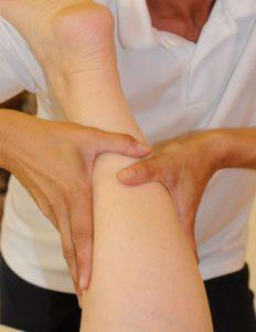 Nahaufnahme der Waden eines am Behandlungsbett liegenden Patienten; die Hände des Therapeuten streichen mit sanftem Druck in Richtung Herz. - Jamina Paukner Pumperlgsund