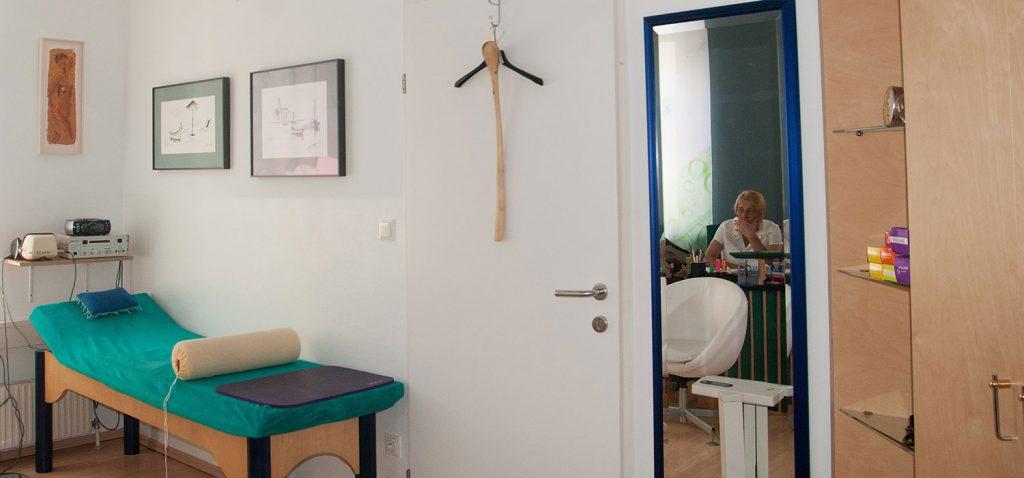 Ordinationsbild, im Vordergrund ein Behandlungsraum mit grüner Liege. Von dort Blick ins Besprechungszimmer; Dr. Ingrid Rapatz, Privatärztin, Gesamtheitsmedizinerin und Ärztin für Schönheitsmedizin in einer Besprechung. - Jamina Paukner/Pumperlgsund