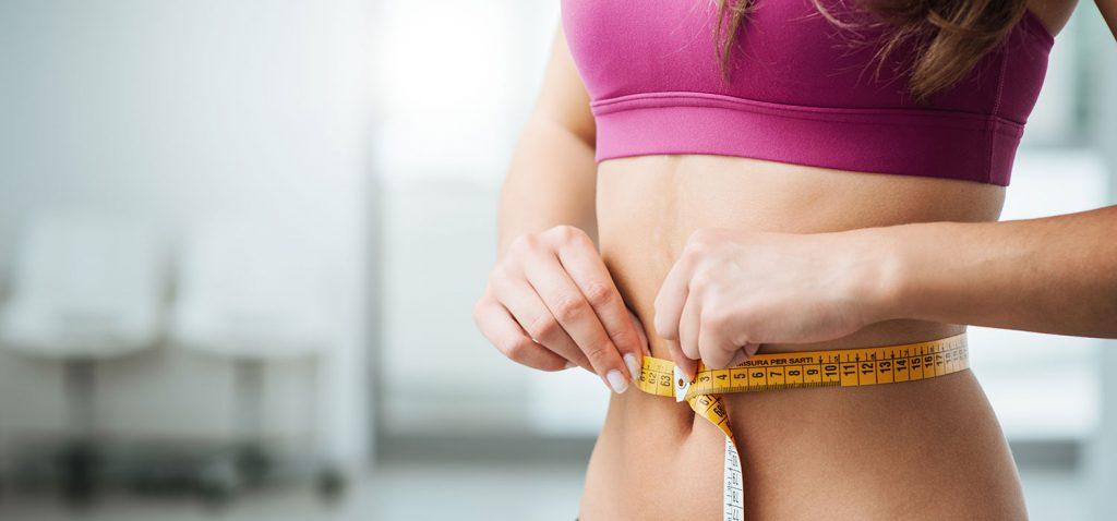 Nahaufnahme des Oberkörpers einer Frau, die mit einem Metermaß ihre Taille vermisst. - Stock-Asso//Shutterstock.com