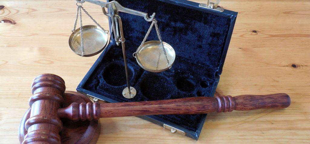 Symbolbild zum Thema Impressum: Kleine silberne Waage in geöffnetem mit blauem Samt ausgekleidetem Koffer.