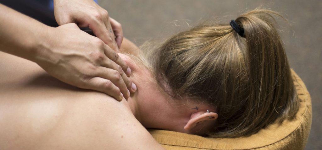 Frau in Nahaufnahme, auf Massagebett am Bauch liegend, erhält Nacken-Massage.