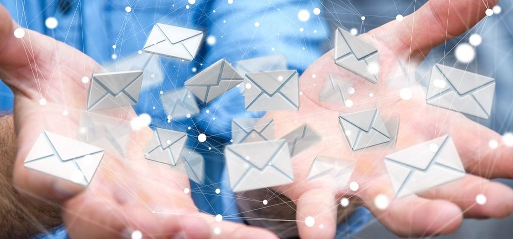 Symbolbild: Blauer Hintergrund, geöffnete Hände in Nahaufnahme werfen viele kleine E-Mail-Kuvert-Symbole in die Luft - sdecoret/Shutterstock.com