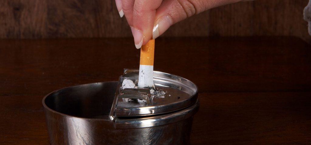 Männerhand, die in einem Aschbecher akurat eine Zigarette ausdämpft. - Anneka/Shutterstock.com