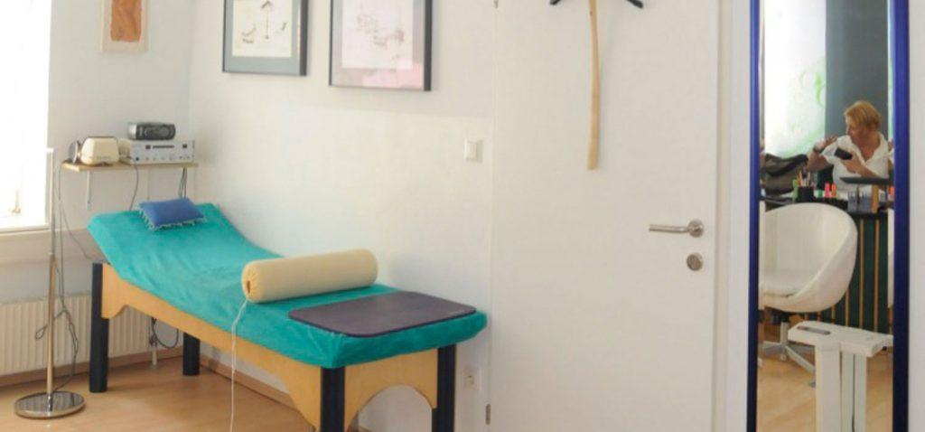 Foto der Ordination mit Behandlungsraum und Blick auf Dr. Ingrid Rapatz, die im Ärtzezimmer in einer Besprechung ist. - Jamina Paukner/Pumperlgsund