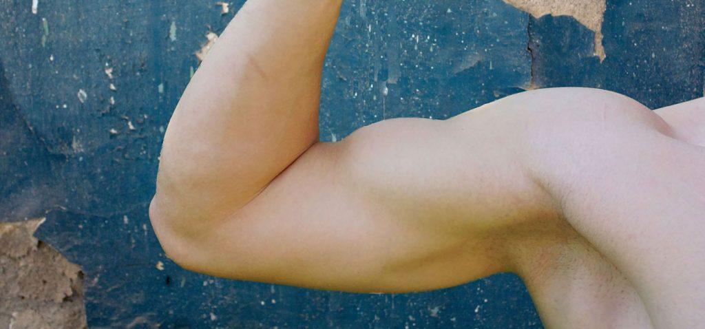 Muskel bepackter männlicher Oberarm in Nahaufnahme.