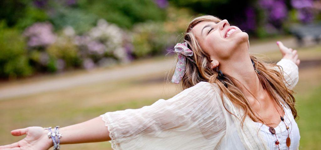 Glückliche Frau mit ausgebreiteten Armen, geschlossenen Augen und breitem Lächeln. - ESB Professional/Shutterstock.com