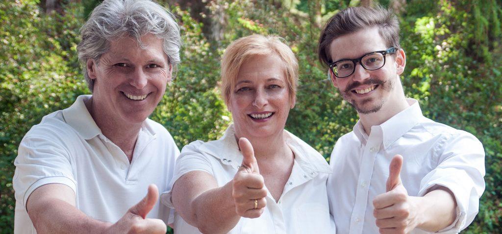 Gruppenbild von Martin Blasl, Dr. Ingrid Rapatz und Hubert Altmann, stehend mit hochgehobenen Daumen. - Jamina Paukner/Pumperlgsund