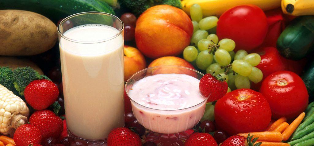 Stilleben-Foto mit zahlreichem frischem, vitaminreichem Obst und Gemüse sowie einem Glas Milch und einer Schale Erdbeer-Yoghurt.